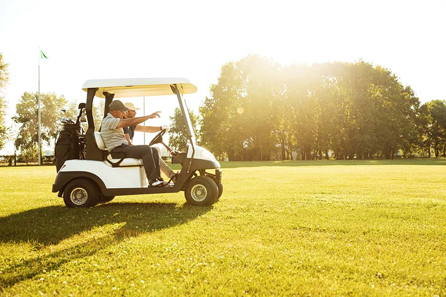 Specialized Business Insurance - Two Friends Driving Around a Golf Course in a Golf Cart